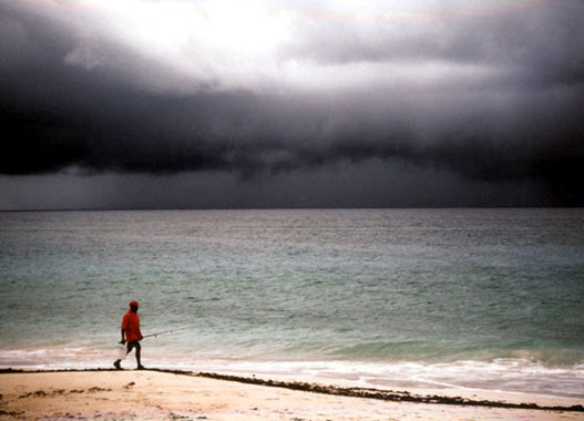 man walking along the beach with a fishing rod in his hand, thunder looming in the sky