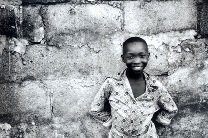 young boy in the village of Moshi, Tanzania standing against a crumbling textured wall