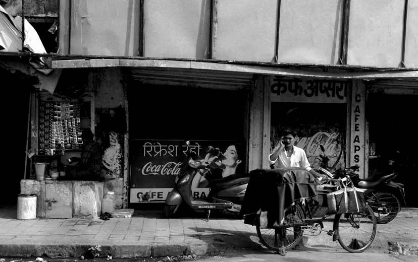 an indian street scene where a man with his bike is talking on a mobile phone outside a rundown building