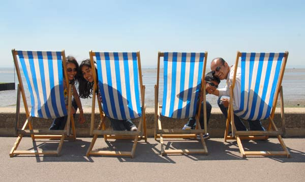 a family of four sitting on deck chairs in the sun