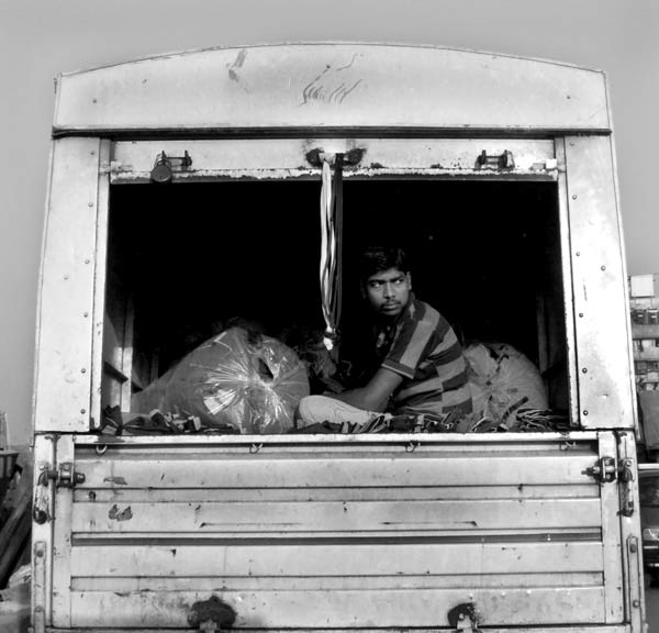 a man sits at the back of an open truck on the road in india
