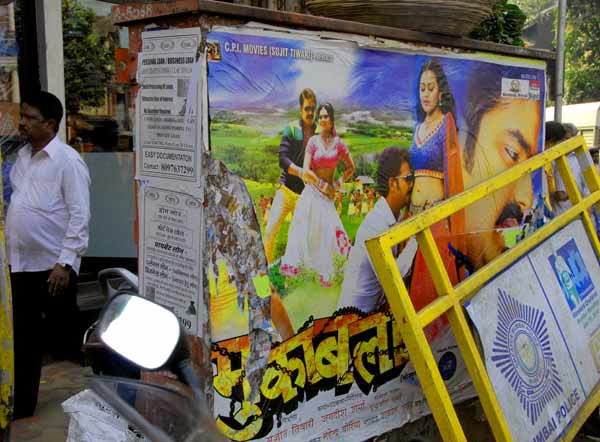 vibrant street scene in India depicting movie posters, rubbish and a man walking by