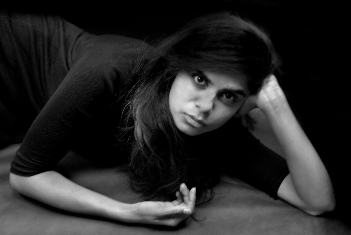 portrait of a young woman laying on the floor leaning over on one arm
