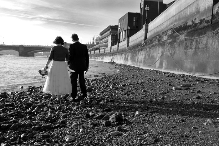 a newly wed couple walk hand in hand along a river