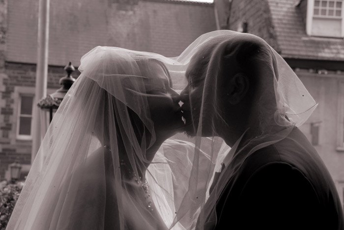 a bride and groom kiss under the brides veil