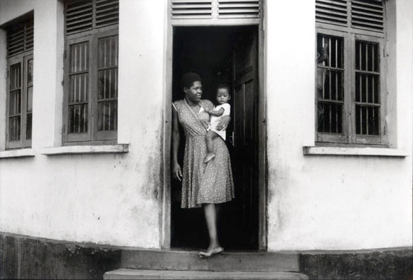 a house in a village in Tanzania where a woman is standing in the open doorway with her child on her hip. A small child peers out of the barred up window